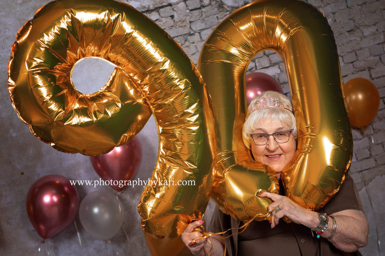 90 year old woman Ellen McGill with head in 90 balloons