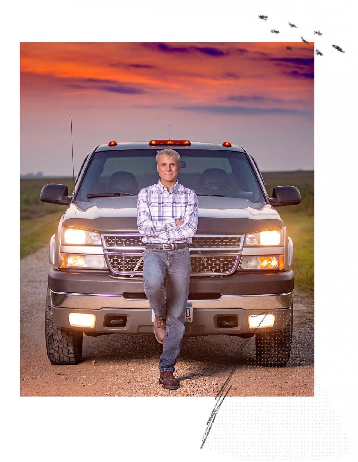 high school senior boy leaning on truck on MN gravel road at sunset